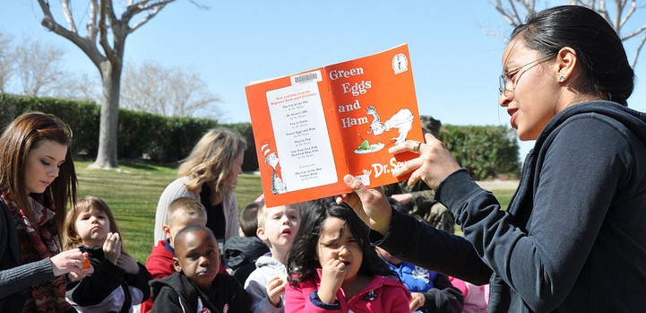 Adult reading book to children outdoors