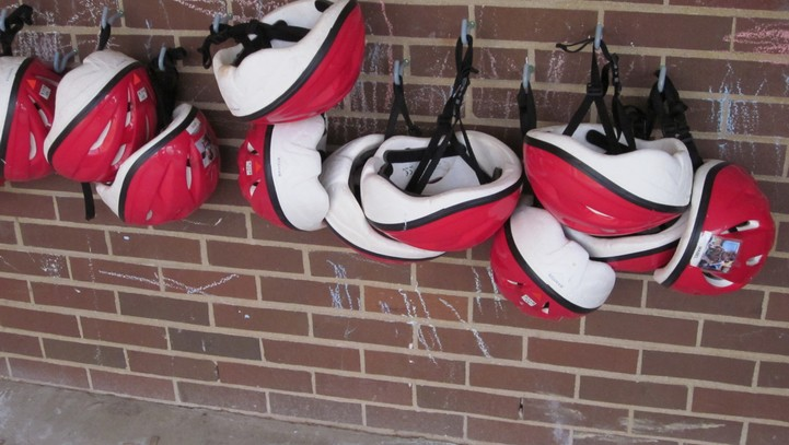 Cihldren's bicycle helmets hanging on a brick wall
