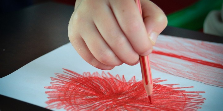 Child drawing with red colored pencil