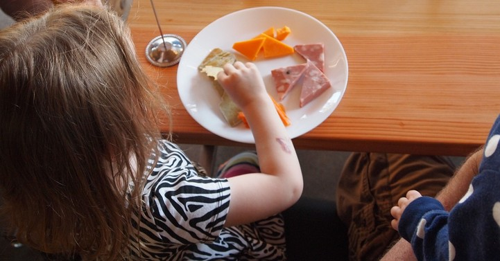 Girl eating cheese and salami