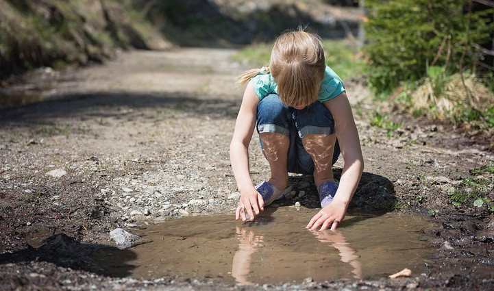 Girl playing in mud puddle