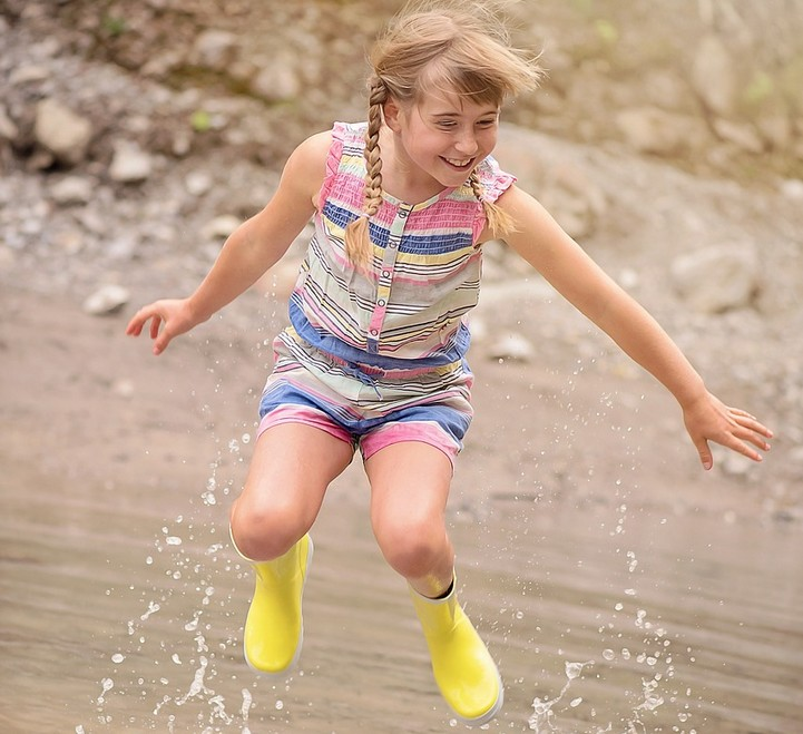 Girl with braids and rain boots jumping