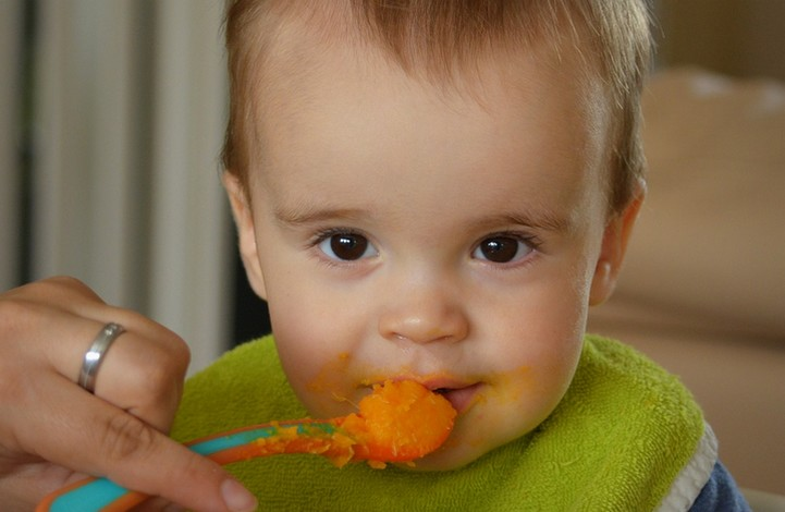 Infant eating baby food from spoon