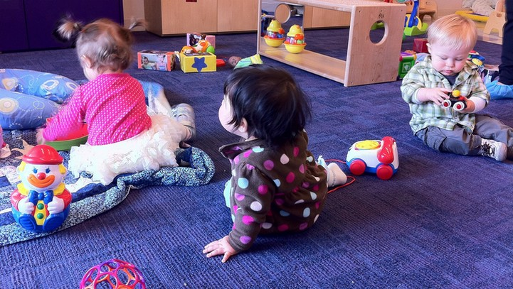 Infants playing on floor in child care